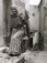 <em>Untitled (Elderly Woman Carrying Jar and Bag),</em>c. 1950s/1960s<br />Gelatin silver print,<br />Image: 11 7/8 x 9""